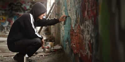 kid spraying graffiti on a wall - juvenile defense