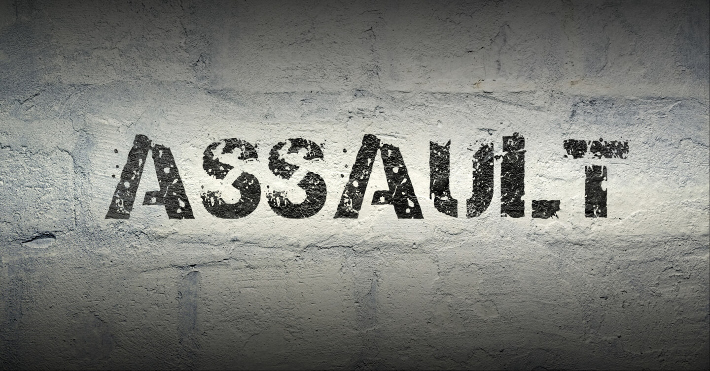 assault written in paint on a brick wall